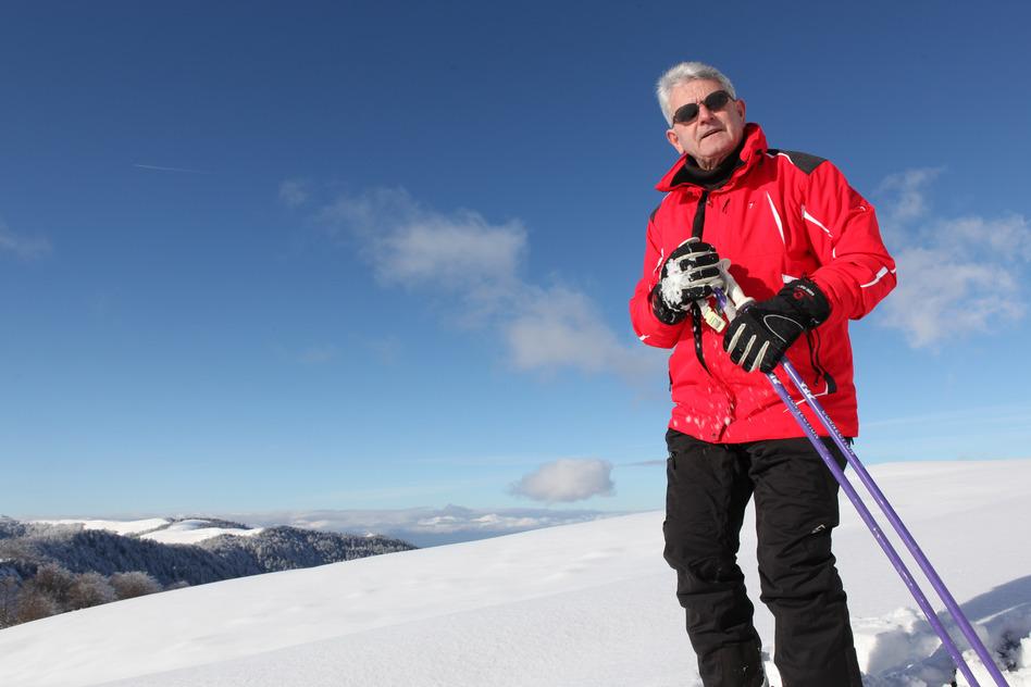 en mand i rød jakke med ski og skihandsker